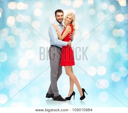 people, valentines day, love, couple and christmas concept - happy young woman and man hugging over blue holidays lights background
