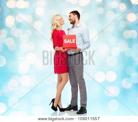 people, sale, discount and christmas concept - happy couple with red sale sign over blue holidays lights background