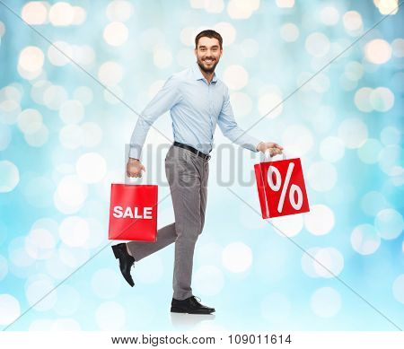 people, sale, discount and christmas concept - smiling man walking with red shopping bags over blue holidays lights background
