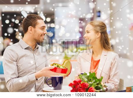 love, romance, valentines day, couple and people concept - happy young couple with red flowers and open chocolate box in at cafe mall with snow effect