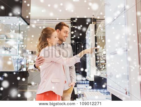 sale, consumerism and people concept - happy couple pointing finger to shopping window at jewelry store in mall with snow effect