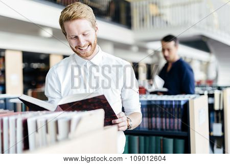 Handsome Student Reading A Book In A Library