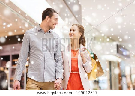 sale, consumerism and people concept - happy young couple with shopping bags walking and talking in mall with snow effect