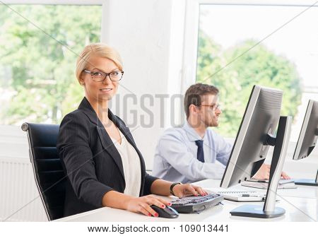 Beautiful female office worker in formalwear with colleague on background.