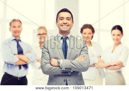 business, people and office concept - happy smiling business team over office room background