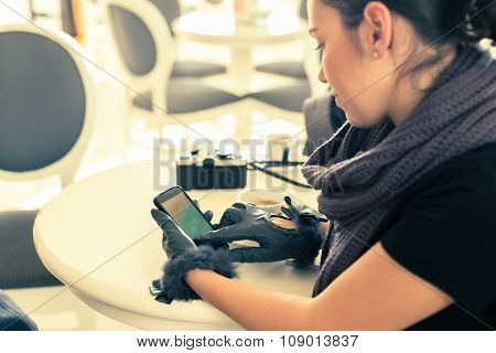 Woman Sitting At Cafe And Chatting With Smartphone