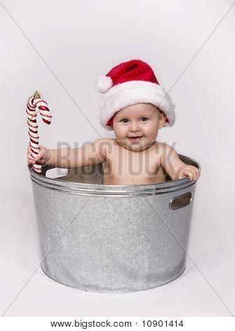 Bebê na bacia segurando o bastão de doces e vestindo chapéu de Papai Noel