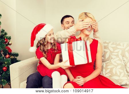 family, christmas, x-mas, happiness and people concept - smiling father and daughter surprise mother with big gift box