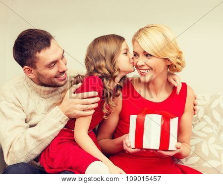 family, christmas, x-mas, happiness and people concept - adorable child kisses her mother and gives present