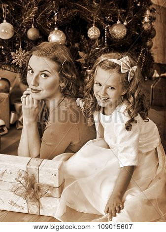 Child with mother waiting father near Christmas tree. Black and white retro vintage.