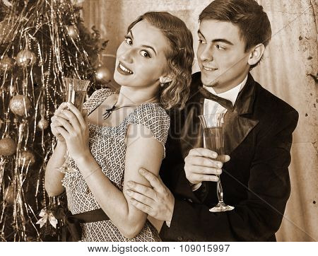 Couple on party flirting and drinking champagne near Christmas tree. Black and white retro vintage.