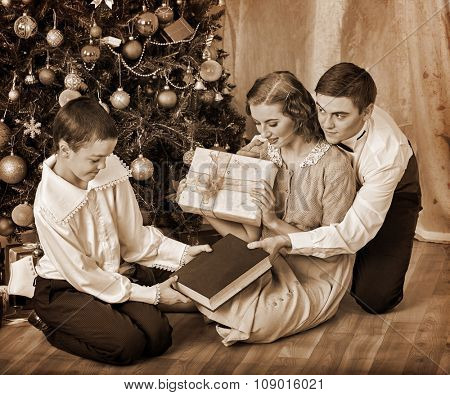 Boy receiving book gift and other presents from his family  under Christmas tree. Black and white retro vintage.