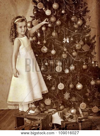 Little girl at chair decorate on Christmas tree. Black and white retro vintage.