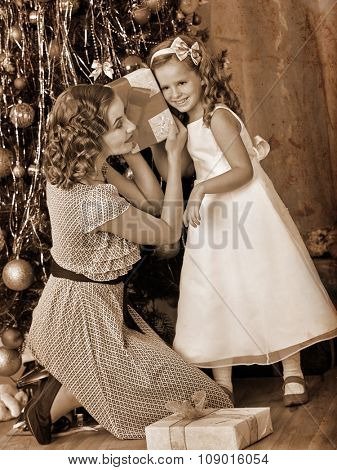 Child with mother receiving gifts under Christmas tree and laughing . Black and white retro.