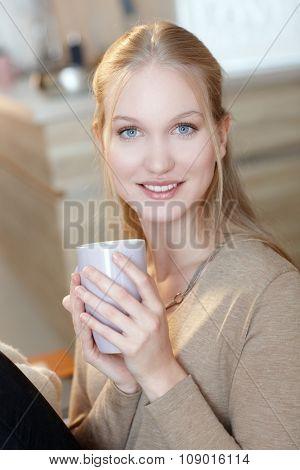 Happy young nordic woman holding tea mug, smiling, looking at camera.