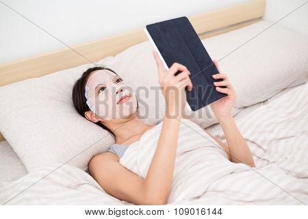 Asian woman lay down in bed with use of the paper mask and digital tablet pc
