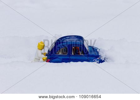 Man pushing car stuck in the snow. Toy models.