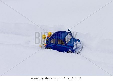 Two men pushing car stuck in the snow. Toy models.