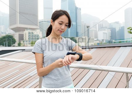 Young Woman checking the data on sport watch at outdoor