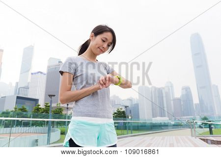 Asian Woman look at the sport watch after running