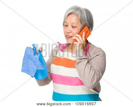 Asian Old woman chat on mobile phone while holding up rag and bottle spray