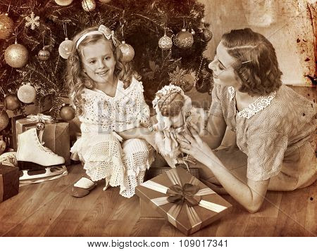Girl with mother receiving old doll gifts lying under Christmas tree. Black and white retro vintage.