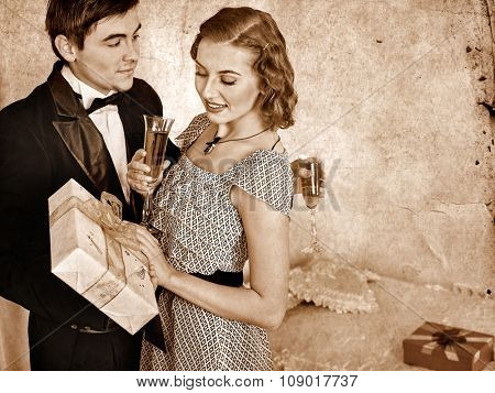 Couple on party drinking champagne and exchange gifts . Black and white retro vintage.