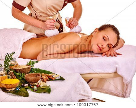 Lying nice woman getting herbal ball massage treatments  in spa.