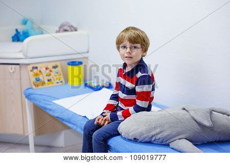 Kid boy with glasses waiting for check-up of pediatrician doctor