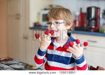 Kid boy eating fresh raspberries in kindergarten