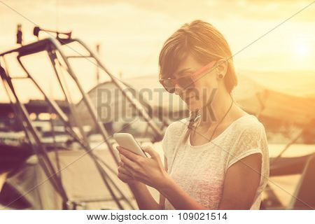 Girl typing messages on a pier with speedboats.