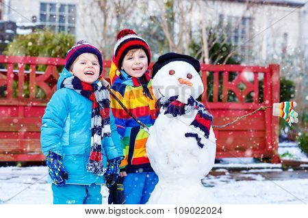 Two little siblings boys making a snowman in winter
