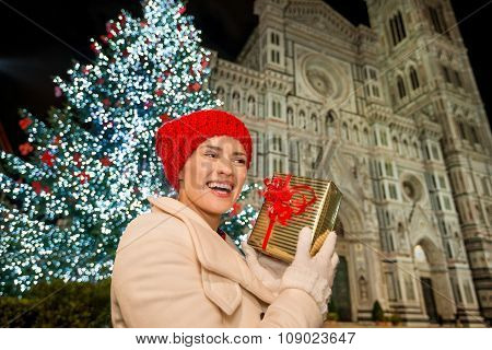 Young Woman With Gift Box Near Christmas Tree In Florence, Italy