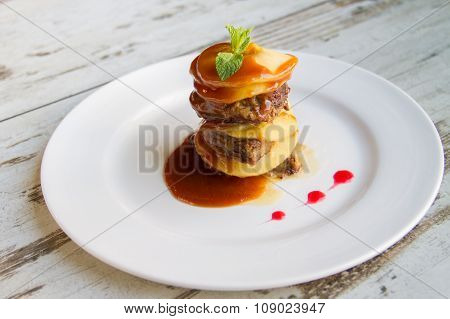 Calf's Liver With Apples Laid Layers With Sauce On A White Plate