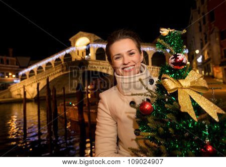 Woman Holding Christmas Tree Near Rialto Bridge In Venice, Italy
