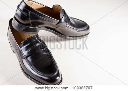 Footwear Concepts. Pair Of Stylish Fashionable Real Leather Black Penny Loafers. Placed On White Sur