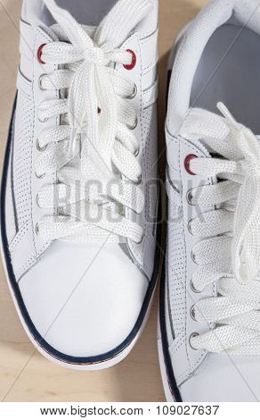 Fashion Concept And Ideas. Closeup Of Pair Of White Fashionable Laced Trainers On Wooden Surface.