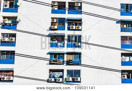 Facade Of Skyscraper With Appartments In Bangkok And Balcnoies With Clothes For Drying