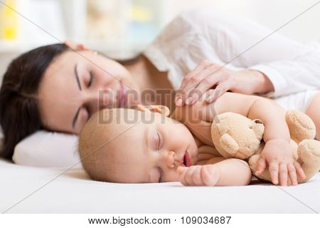 beautiful woman and baby sleeping together in a bedroom