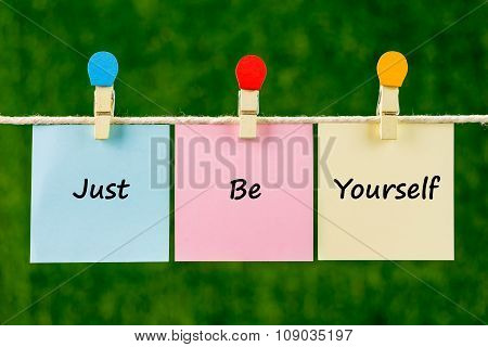 Words Of Just Be Yourself On Sticky Color Papers Hanging By A Rope.