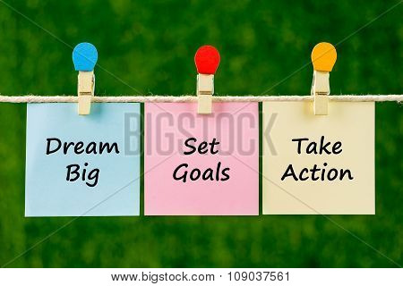 Words Of Dream Big, Set Goals, Take Action On Sticky Color Papers Hanging By A Rope.