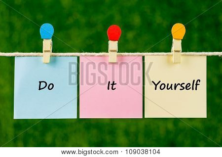 Words Of Do It Yourself On Sticky Color Papers Hanging By A Rope.