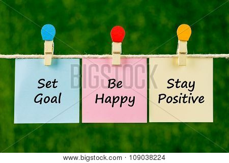 Word Quotes Of Set Goal, Be Happy, Stay Positive On Sticky Color Papers Hanging On Rope.