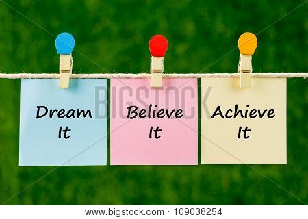 Word Quotes Of Dream It, Believe It, Achieve It On Sticky Color Papers Hanging On Rope.