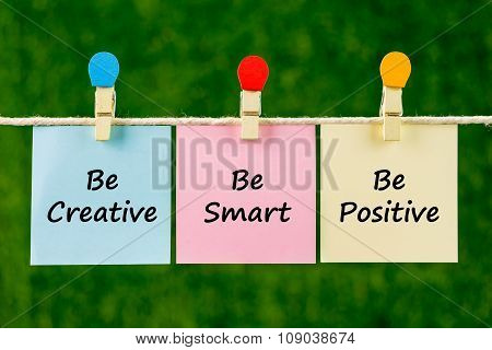 Word Quotes Of Be Creative, Be Smart, Be Positive On Sticky Color Papers Hanging On Rope.