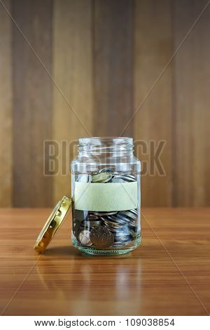 Image Of Coins In Clear Bottle With Blank Label Against Blurred Wooden Background.