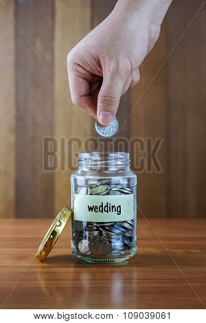 Image Of Hands Putting Coin Into Clear Bottle With Wedding Label Against Blurred Wooden Background.