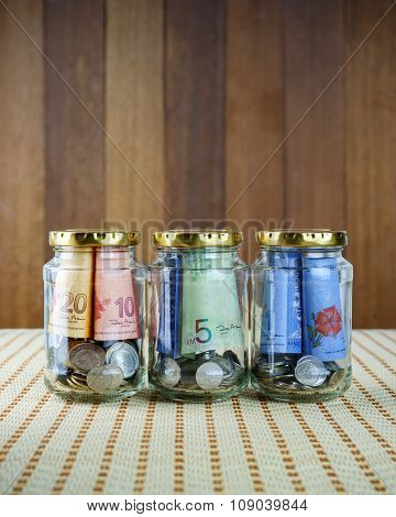 Image Of Money In Three Clear Bottles.