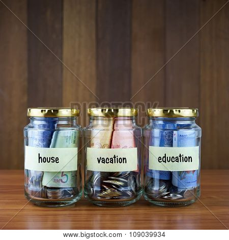 Image Of Money In Clear Bottles With House, Vacation, Education Labels.