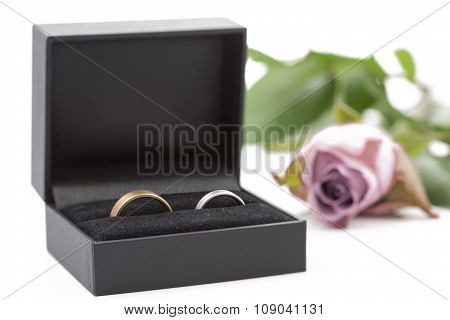 Two wedding rings in a jewelry box on white